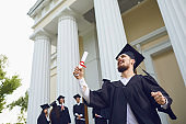The guy with the scroll is smiling against the background of university graduates.