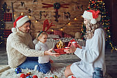 Parents gives gifts to the child in the room in Christmas