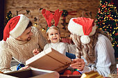 The family gives gifts to the child in the room in Christmas