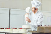 Confectioner decorating cake in pastry shop.