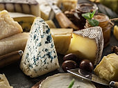 Segment of blue mould cheese with olives and range of cheeses at the background.