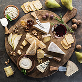 Cheese platter with different cheeses, fruits, nuts and wine on stone background.