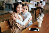 Serene young woman and her daughter sitting in embrace while relaxing in cafe