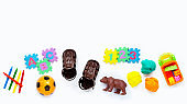 Brown leather children's sandals with colorful  toys on white background. Copy space