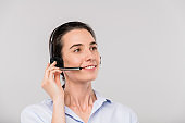Happy young brunette operator with headset talking to clients online
