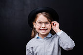 Pretty little girl looking at you with toothy smile while touching eyeglasses