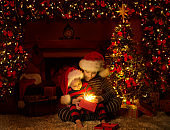 Christmas Kids Opening Lighting Presents Gifts under Xmas Tree, Child and Baby Boys in Red Santa Hats