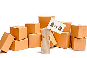 A wooden figurine of a person stands near a pile of boxes and raises the question of how to transport the goods from one house to another. The concept of moving to a new home, transportation companies