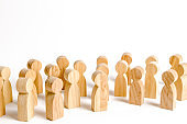 A crowd of wooden figures of people on a white background. Social survey and public opinion, the electorate. Population and citizens. Human resource, search for candidates for work.
