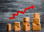 a red arrow up above cardboard boxes folded incrementally. Sales growth and increase in exports of goods and services. Growth profits and the number of buyers.