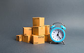 A stack of cardboard boxes and a blue alarm clock. Express delivery concept. Temporary storage, limited offer and discount. Optimization of logistics and delivery, improving efficiency, reducing costs
