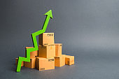 A pile of cardboard boxes and a green up arrow. The growth rate of production of goods and products, increasing economic indicators. Increasing consumer demand, increasing exports or imports.