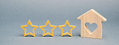 Three stars and a wooden house on a gray background. Rating and status of the restaurant. Prestige. High quality. Evaluation of the critic. Review and feedback. Hotel for lovers. Rating. Hospitality