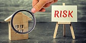 Miniature wooden house and the inscription ' Risk ' . Buying a house, apartment and financial risks. Loss of property for failure to pay. Property insurance. Mortgage and tax. Real estate