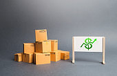 A pile of cardboard boxes and whiteboard with dollar sign and green up arrow. The growth rate of production. Increasing consumer demand. Growth of income from the sale of goods. Price increase.