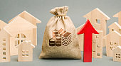 Red arrow up, money bag and miniature wooden houses. The concept of rising property prices. High mortgage rates. Expensive rental apartment. Growing demand for home purchase. Real estate market.