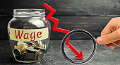 Glass jar with coins and the word Wage and a red down arrow. Salary reduction. Drop in profits. Financial crisis. Demotion. Low profit. Capital outflow. Concept of business and finance