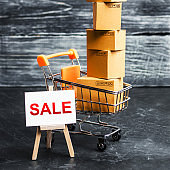 A shopping cart filled with cardboard boxes and an easel with the word Sale. Advertising sale, marketing. Business strategy analysis. Discount. Shopping online. Attracting customers at low prices.