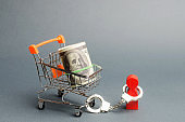Person is handcuffed to a bundle of money on a supermarket cart. A person is limited by the burden of a large debt or liabilities, an outstanding loan and mortgage, a difficult financial situation