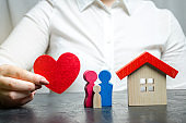 A woman holds in her hands a red heart near a miniature family and home. The concept of property insurance and house. Home Security. Life and health insurance. Protection and safety. Agent