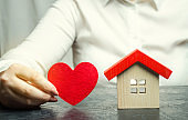 A woman holds a red heart near the wooden house. Insurance agent services. Property insurance concept. Protection of housing. Security and safety family and life. Protect the home. Support