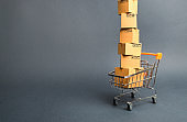 High tower of cardboard boxes on a supermarket trolley. concept of shopping in online store. E-commerce, sales and sale of goods through online trading platforms. Consumer society. Purchasing power