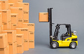 Yellow Forklift truck picks up a box on a pile of boxes. Service storage of goods in a warehouse, delivery and transportation. Freight shipping, delivery. Import and export, commodity exchange