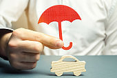 An insurance agent is holding a red umbrella over a miniature wooden car. Auto insurance concept. Vehicle protection. Insurance company services. Gesture of protection. Safety and security