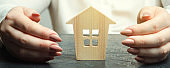 A woman is protecting a miniature wooden house. Property insurance concept. Protection of housing. Security and safety. Family and life insurance. Service. Agent. Support