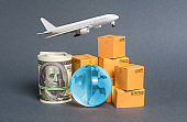 A stack of boxes, airplane a bundle of dollars and a blue planet earth globe. World trade and commodity exchange. commerce traffic trading balance. Import, export, transit of products.
