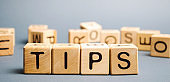 Wooden blocks with the word Tips and randomly scattered cubes. Award for good service in the cafe restaurant. A gratuity is a sum of money customarily given by a client or customer to a service worker