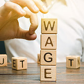 Hand of a businessman removes wooden blocks with the word Wage. Salary reduction concept. Wages cuts. The concept of limited profit. Lack of money and poverty. Small income.