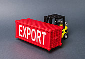 A forklift carries a red freight container labeled Export. concept transportation of goods and products, delivery, shipping. Industry and production, trade balance and distribution. Globalization