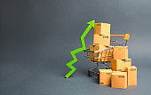 Shopping cart with cardboard boxes and a green up arrow. Increase the pace of sales and production of goods. Improving consumer sentiment, economic growth. Strategy for increasing revenue