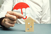 An insurance agent is holding a red umbrella over a wooden house. Property insurance concept. Protection of housing / house. Security and safety. Family, life and housing insurance. Service