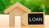 Miniature house with the word Loan. The concept of mortgage housing and real estate loans. Buy an apartment on credit. Leasing. Affordable Housing for young families. Interest rates
