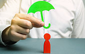 An insurance agent holds a green umbrella over a human figure. Concept of life and health insurance. Unconditional income. Protection of rights. Security. Legal assistance. Golden parachute
