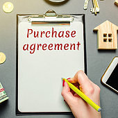 Table with wooden houses, calculator, magnifying glass with the word Purchase agreement. The concept of real estate purchase. Buy an apartment or house. Buying housing. Property. Sign a contract