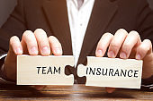 Businessman collects puzzles with the words Team Insurance. Security and safety in a business team. Care for employees. A responsibility. Employee confidence in protection. Health care concept