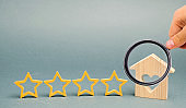 Four stars and a wooden house on a gray background. Success. Feedback. Good evaluation of the critic. Hotel rating. Quality of service. Overview. Restaurant. Housing. Customer