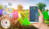 Farmer holds smartphone with infographic on tractor background with potato digger. Farming and smart agriculture. Agricultural machinery, data analyzing on plants status. Harvesting.