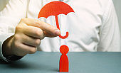An insurance agent holds a red umbrella over a human figure. Concept of life and health insurance. Unconditional income. Protection of rights. Security. Legal assistance. Golden parachute