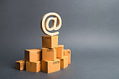 The email symbol commercial AT is on cardboard boxes stack. E-commerce. automation and development of logistics supplies, reducing personnel costs, storage. Internet sales. network trading