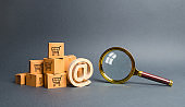 Pile of cardboard boxes with email symbol commercial AT and magnifying glass. online shopping and commerce. Search engine and filtering. purchase through the Internet. online trading platforms.