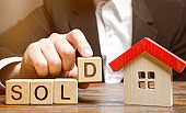 A realtor holds blocks with the word Sold near a miniature wooden house. Real estate market. Selling a house, apartment. Trade of property. Affordable housing. Real estate agent services.