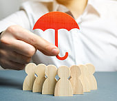 Boss holding a red umbrella and defending his team with a gesture of protection. Security and safety in a business team. Life insurance. Customer care, care for employees. Selective focus
