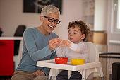 Grandmother feeding her grandson