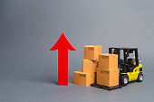 Yellow Forklift truck with cardboard boxes and a big red arrow up. increase in trade between countries, popularity of national goods, economic growth. growth rate of production goods and products,