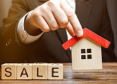 Wooden blocks with the word Sale and miniature house in the hands of a real estate agent. Real estate market. Selling a house, apartment. Trade of property. Affordable housing. Realtor
