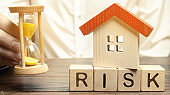 Wooden blocks with the word Risk, the house and the clock. The concept of non-payment of interest rates on mortgages. Real estate investment risk. Loss of property for non-payment. Lack of money